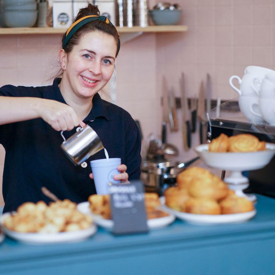 Vrouw schenkt koffie in een herbruikbare beker van Billie Cup